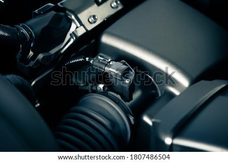 Car mass air flow sensor in the engine room. Car maintenance concept.