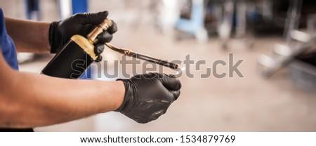 Car master mechanic repairer fire up the butane gas blow mini welding torch bottle heating flamethrower burner in vehicle repair service