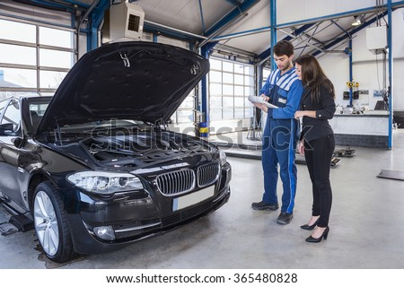 Car mechanic and customer stand next to the serviced car and looking through the checklist. The car had an annual checkup and stands in the garage with the hood open.