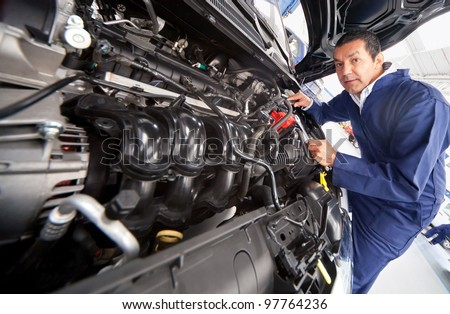 Car mechanic at the garage fixing the engine