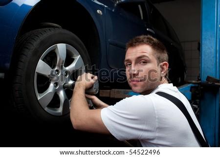 Car mechanic changing wheel in auto rapair shop - stock photo