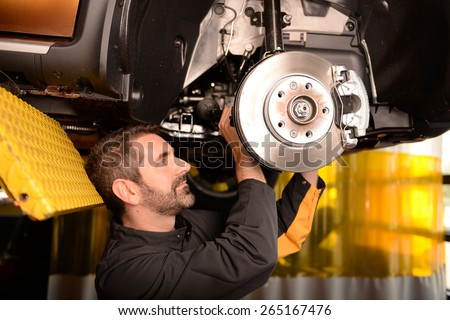 Car mechanic checking car at auto repair shop service station, front or rear axle inspection #265167476