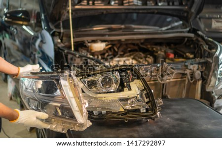 Car mechanic, doing cleaning, The headlight of the car, installation and turning headlight of modern automobile and car projector lens. Vehicle head xenon lamp in details. Concept of auto detailing,  #1417292897