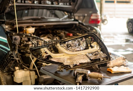 Car mechanic, doing cleaning, The headlight of the car, installation and turning headlight of modern automobile and car projector lens. Vehicle head xenon lamp in details. Concept of auto detailing,  #1417292900