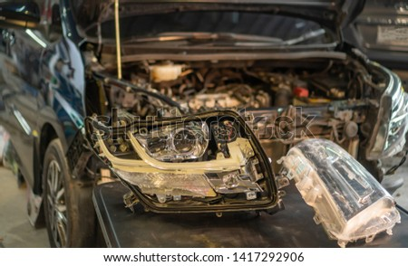 Car mechanic, doing cleaning, The headlight of the car, installation and turning headlight of modern automobile and car projector lens. Vehicle head xenon lamp in details. Concept of auto detailing,  #1417292906