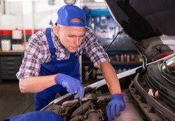 Car mechanic fixing a car engine and repairing checking under the car hood in auto service