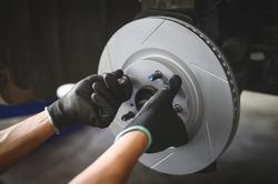 Car mechanic hands installing new six slot Disc Brake Rotor.