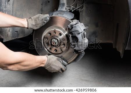 Car mechanic hands replace brakes in garage. Mechanic technician worker installing car wheel at maintenance.  Worker changing brake disc. Brake disc installation concept.