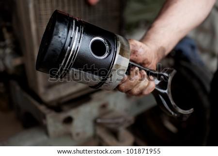 Car mechanic holding engine piston.