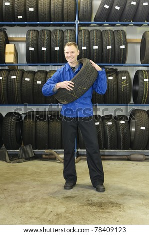 Car mechanic in blue overalls pulls a tire from the tire store in the garage
