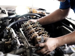 Car mechanic in garage with car engine after remove the cover part.