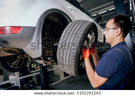 Car mechanic inspecting wheel and suspension detail of lifted automobile at repair service station. Auto service. #1105391243