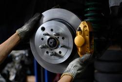 Car mechanic installing two piston brake calipers and disc brake rotor.