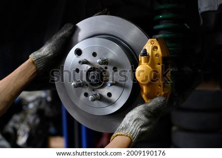 Car mechanic installing two piston brake calipers and disc brake rotor. ストックフォト ©