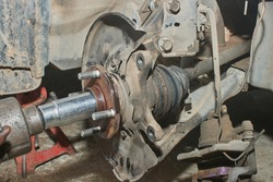 Car Mechanic or Auto Mechanic Tighten Drive Axle Shaft Hub Nut on Wheel Hub by Wind Block and Hang Brake Caliper