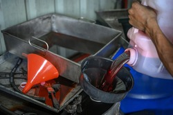 Car mechanic pouring old used automatic transmission fluid into the oil drum.