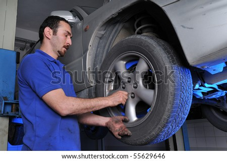 Car mechanic removing wheel nuts to change tire - a series of MECHANIC related images.