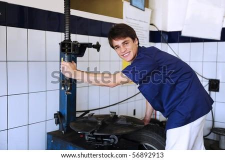 car mechanic repairing tire at the car repair shop