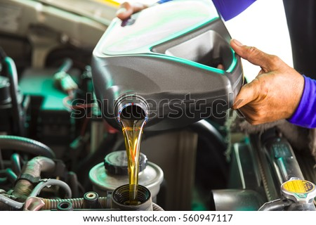 Car mechanic replacing and pouring fresh oil into engine at maintenance repair service station