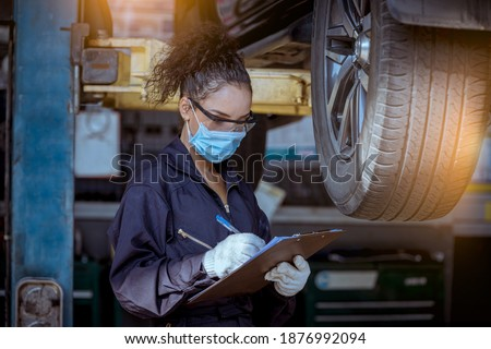 Car mechanic under checking car wheels at garage for maintenance or charge a new new wheel ,they wearing safety uniform, glasses and face mask to work.  Photo stock ©