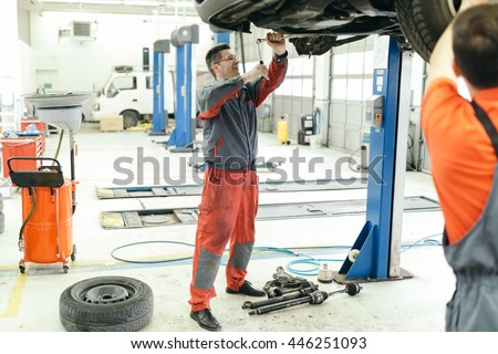 Car mechanic upkeeping car in dealership garage #446251093