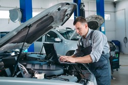 car mechanic using a computer laptop to diagnosing and checking up on car engines parts for fixing and repair