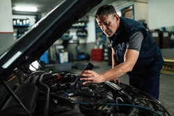 Car mechanic using lamp while examining engine under the hood at auto repair shop.