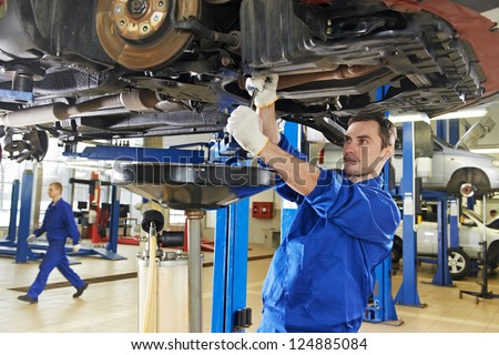 car mechanic with spanner tighten car suspension detail of lifted automobile at repair service station