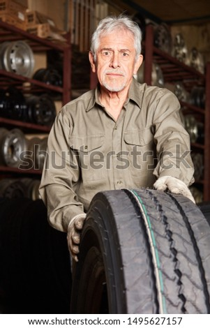 Car mechanic with workshop experience Stock with tire for tire changing #1495627157