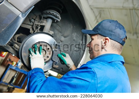 car mechanic worker replacing brakes of lifted automobile at auto repair garage shop station