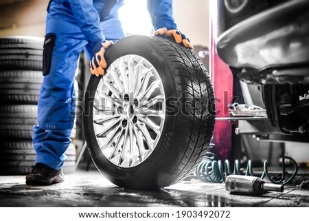 Car mechanic working in garage and changing wheel alloy tire. Repair or maintenance auto service.