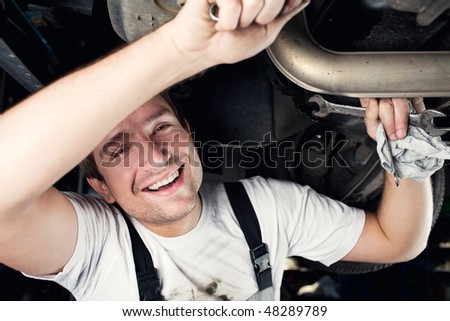 Car mechanic working under the car smiling Car service
