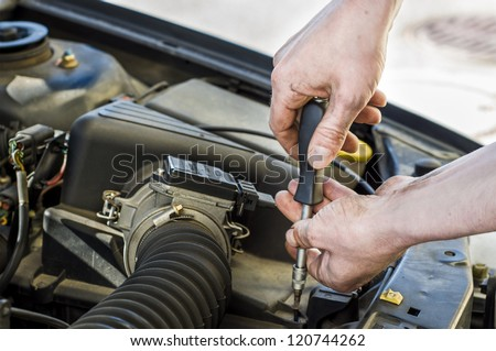 Car mechanic working under the engine hood of a car.