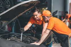 Car mechanics open car hood repairs system checking oil motor level for maintenance and clean in car garage service.