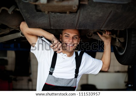 Car mechechanic smiling in car service standing under the car - stock photo