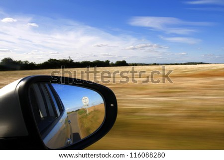 Car mirror with background speed blur