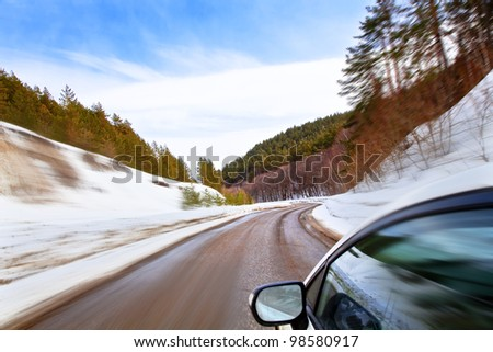 car moves along the winding roads of winter. Winter Landscape, motion blur.