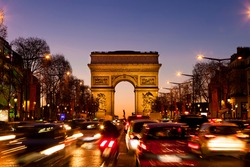 CAR MOVING BY ARC DE TRIOMPHE AT SUNSET