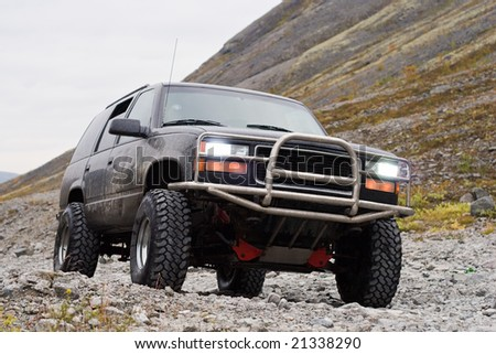 car off-road with switched on headlights on mountain background