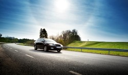Car on asphalt road in beautiful spring day at countryside