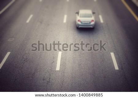 Car on asphalt road with Len blur and Len film.