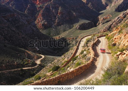 Car on dusty mountain pass winding through dramatic mountains with red rock.
