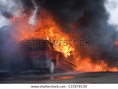 Car on fire after and accident or during a riot.