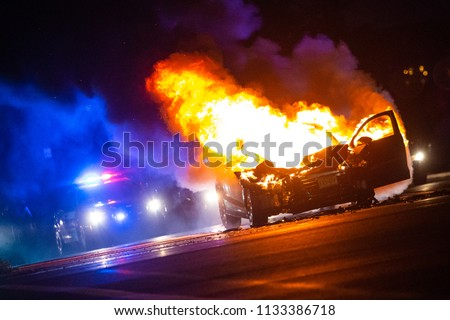 Car on fire at night with police lights in background no one Foto stock ©
