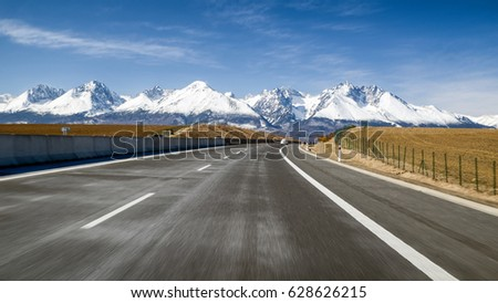 Car on highway D1 and snowy peaks of High Tatras mountains, Slovakia