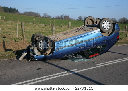 Car on roof after road accident but driver survived