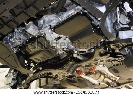 Car on service, lifted on a lift. View of the engine and gearbox from below.