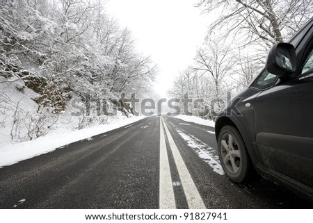 Car on snowy winter road.
