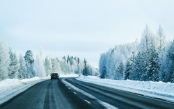 Car on Winter road with snow in Finland. Auto and Cold landscape of Lapland. Automobile on Europe forest. Finnish City highway ride. Roadway and route snowy street trip. Driving