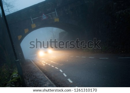 Car or vehicle on the road at night in foggy conditions. Angled dramatic shot showing fog and danger. Passing under arched bridge